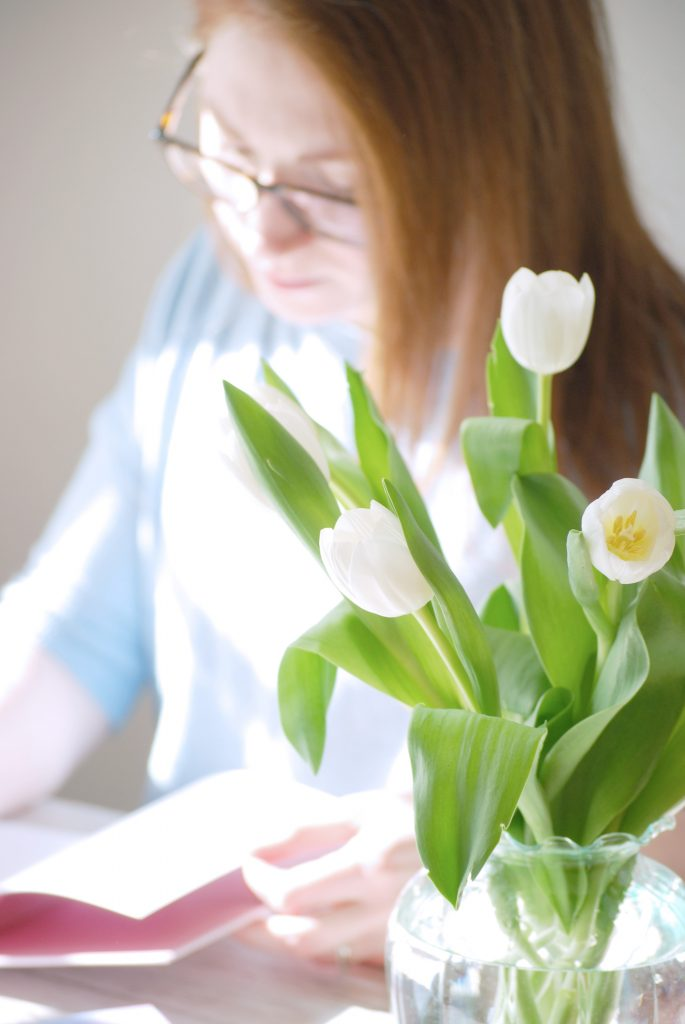 Kerri Awosile artist designer writing blog post at desk with flowers