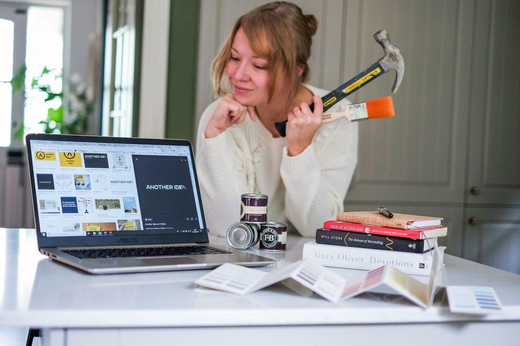 Ceri Olofson, creative copywriter of Candour and Polish, self potrait for Kerri Awosile Creative Business Blog series with books, hammer, and laptop