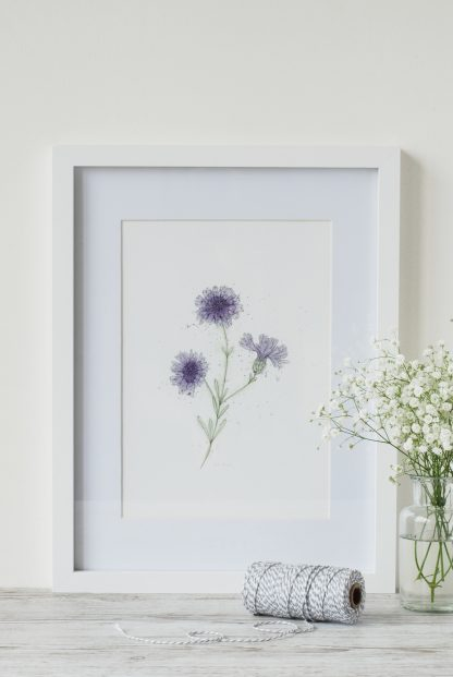 cornflower art print by Kerri Awosile, framed and on table with strong and white flowers