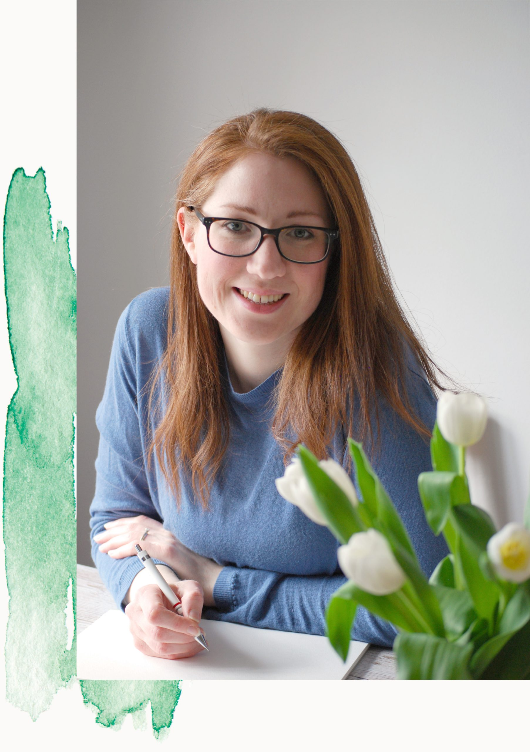 Kerri Awosile - artist, illustrator, writer, and designer in the UK - inspiring creativity for women in the UK through a blog, newsletter, products and creative art, illustration, writing and design services - sitting at desk with white tulips