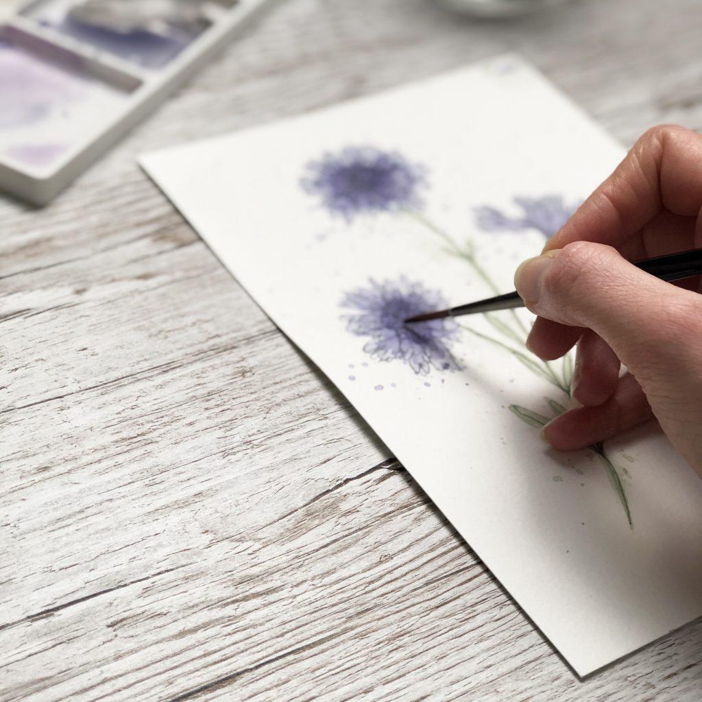 painting cornflower from the new Kerri Awosile product range at artist studio desk