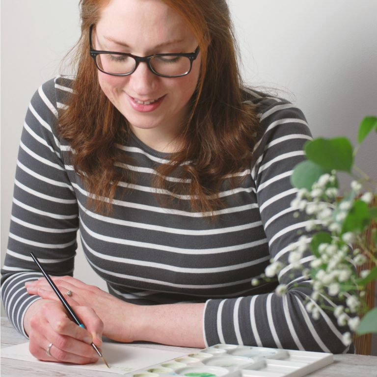 Kerri Awosile - art, writing, design, in UK - painting with striped grey top behind eucalyptus