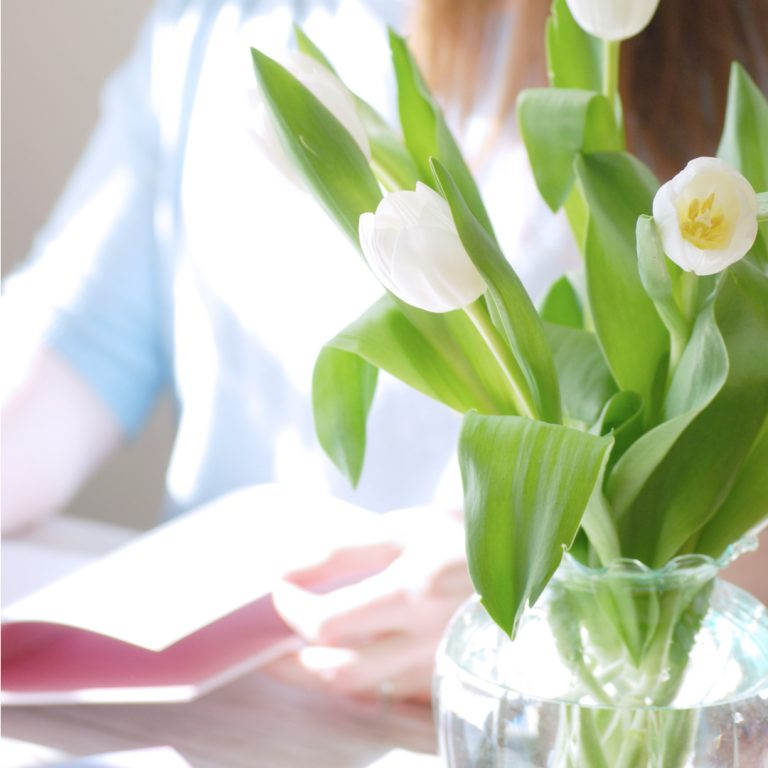 Kerri Awosile making notes in notebook behind white and green tulips