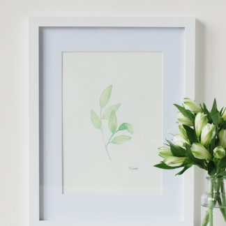 original fresh green leaves watercolour painting by Kerri Awosile, framed and on table with white flowers