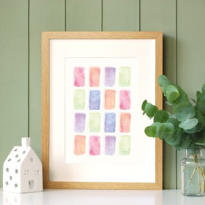 A Colourful Life watercolour art print by Kerri Awosile in oak frame with green paneling wall and eucalyptus