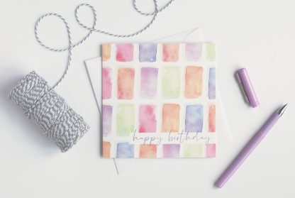 colourful watercolour happy birthday card on table with string and purple pen
