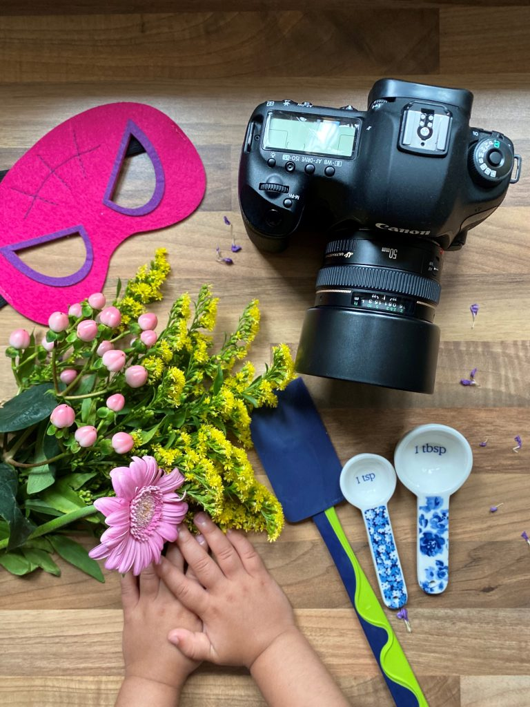 Self-portrait by Deepa Rodrigues with camera, hero mask, flowers, baking tools, and child's hands