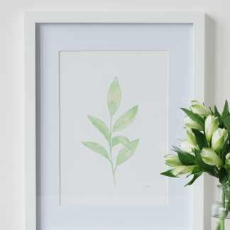 Green Leaves watercolour art print by Kerri Awosile, framed, and with white flowers and paint palette on table