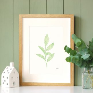 Green Leaves watercolour art print by Kerri Awosile in oak frame with green paneling wall and eycalyptus
