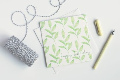 Green Leaves Watercolour Happy Birthday Card by Kerri Awosile on table with string and yellow pen