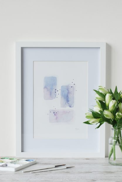 'Purple Morning Abstract' watercolour painting, framed and with white alstromeria flowers and a pain palette and brushes on table