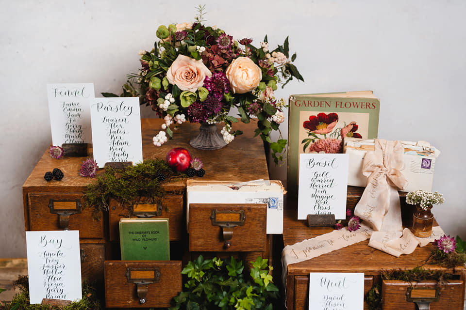 Kirsten Butler's styling set up with table plan, books, drawers, and flowers, as The Little Wedding Helper