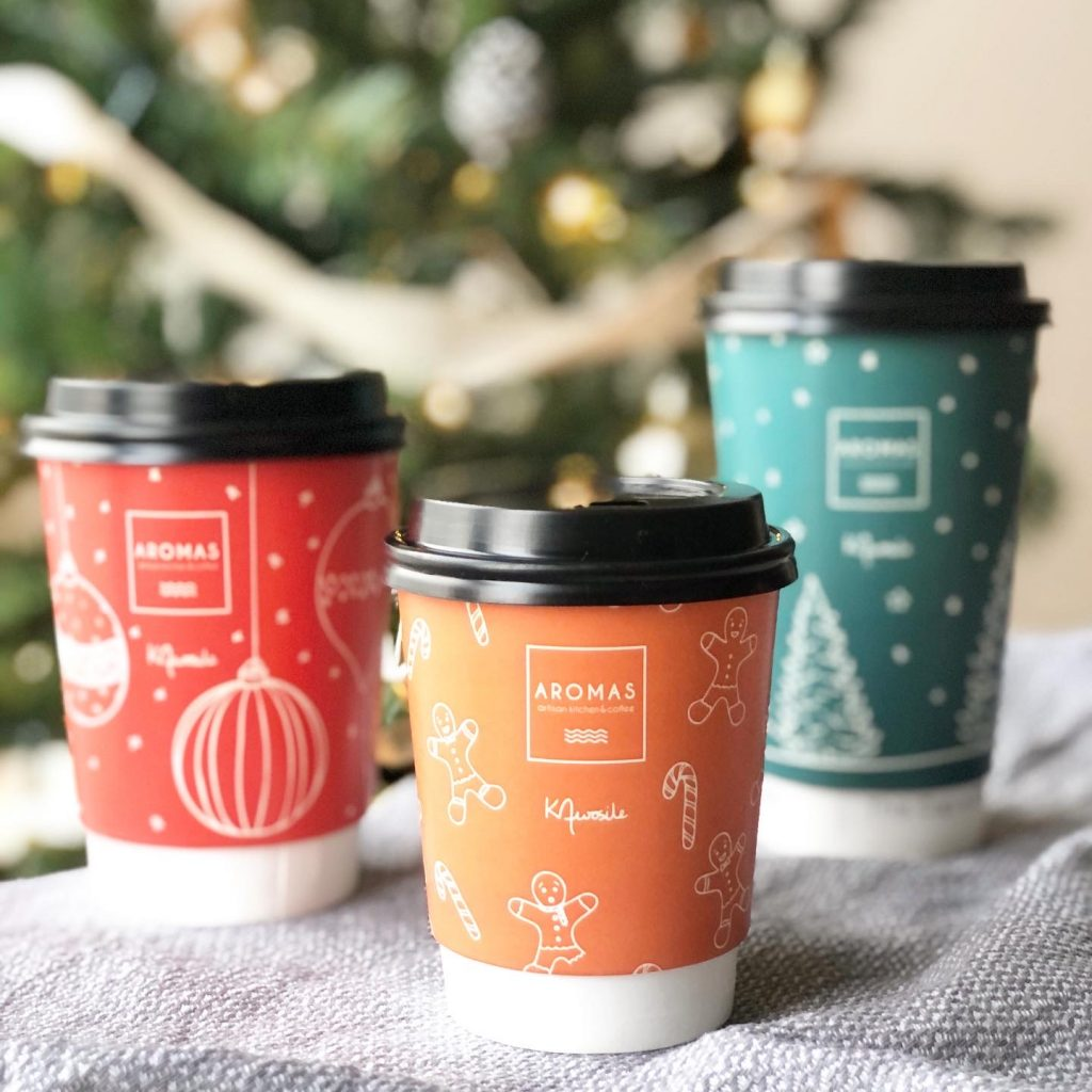 Aromas cafe Christmas take-away coffee cup designs with line-art illustrations by Surrey artist Kerri Awosile with Chrismtas tree and lights in background