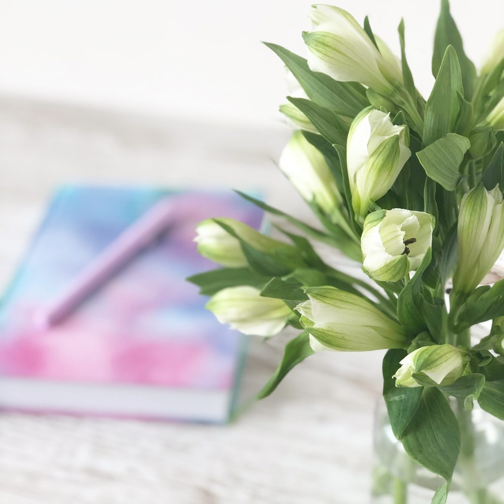 purple, pink, and blue notebook with pen on desk with vase of white and green flowers