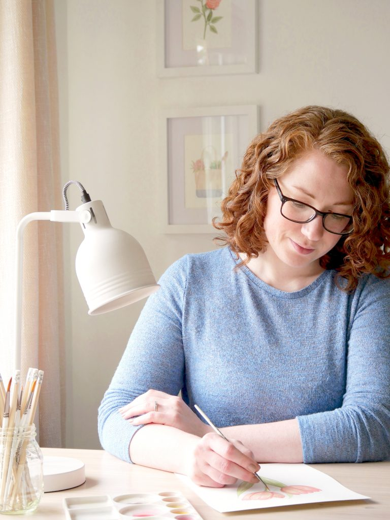 Kerri Awosile artists in Surrey UK, painting at her desk with white lamp and neutral pencils